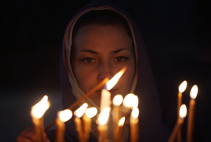 A woman lights a candle in the Church of the Nativity in the West Bank town of Bethlehem December 2. The church is the oldest in the Holy Land still used for regular worship. In the grotto of the church, a silver star marks the site of Christ's birth (CNS photo/Mohamad Torokman, Reuters).
