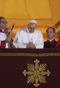 Pope Francis leads a prayer as he appears for the first time on the central balcony of St. Peter's Basilica on March 13 (CNS photos)