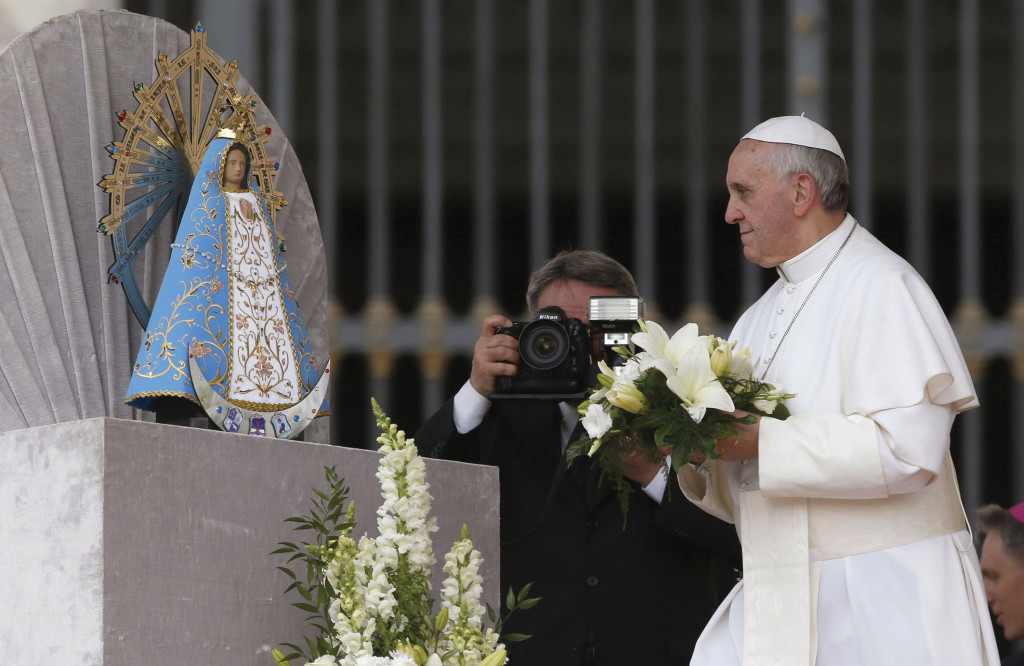 Pope Francis offers flowers before a statue of Our Lady of Lujan during his weekly audience in St. Peter's Square at the Vatican May 8 (CNS photo)