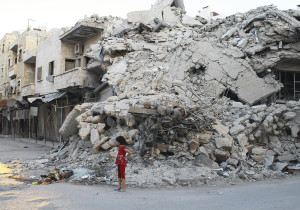In this Sept. 8 photo, a girl stands in front of a building destroyed by what activists said was shelling by forces loyal to Syrian President Bashar Assad in the northern town of Ariha, Syria.