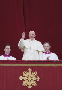 Pope Francis waves a he delivers his Christmas blessing (to the city and the world) form the central balcony at St. Peter's Basilica at the Vatican December 25.