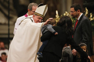 The Pope greets a child during Christmas Midnight Mass in St. Peter's Basilica on December 24  (Galazka photo)