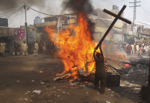 A demonstrator burns a cross during a protest in the Badami Bagh area of Lahore, Pakistan, March 9, 2013.