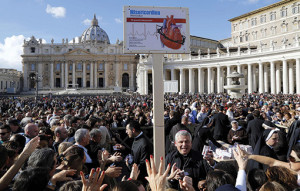 """Archbishop Konrad Krajewski, director of papal charities, helps distribute boxes of """"spiritual medicine"""" in St. Peter's Square after Pope Francis' recitation of the Angelus at the Vatican Nov. 17 (CNS photo)."""