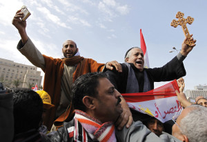 A Muslim holding the Koran and a Coptic Christian holding a cross are carried through demonstrators in Tahrir Square in Cairo in 2011 (CNS photo).