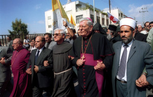 The sheik of Jerusalem (on the right) holds hands with Msgr. Pietro Sambi, papal nuncio to Israel, during a march for peace into Betlehem on October 23, 2001.