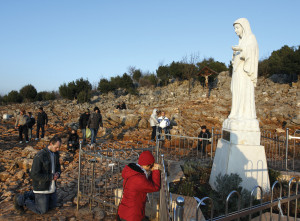 Pilgrims prat at a statue of Mary in 2011 on Apparition Hill in Medjugorje.