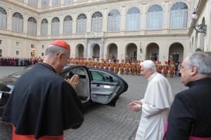 """Cardinal Bertone, with his back to the camera, gestures as Pope Benedict XVI leaves the Vatican for Castel Gandolfo, Italy, on February 28, 2013. """"I am a simple pilgrim who begins the last stage of his pilgrimage on this earth,"""" the Pope said at the close of his papacy."""