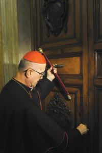 """Italian Cardinal Tarcisio Bertone seals the door of the Pope's private apartment in the Apostolic Palace at the Vatican February 28. As camerlengo (""""chamberlain""""), Cardinal Bertone was charged with administering the temporal goods of the Church following the resignation of Pope Benedict XVI."""