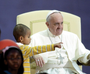 October 26, 2013, a little child comes up to Francis during his meeting with families.