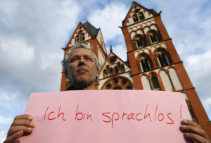 """A protester holds a placard reading: """"I'm speechless!""""."""