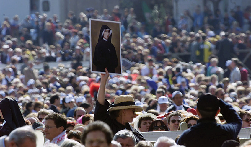 A woman is holding up Maria Faustina Kowalska's portrait before the canonization ceremony.