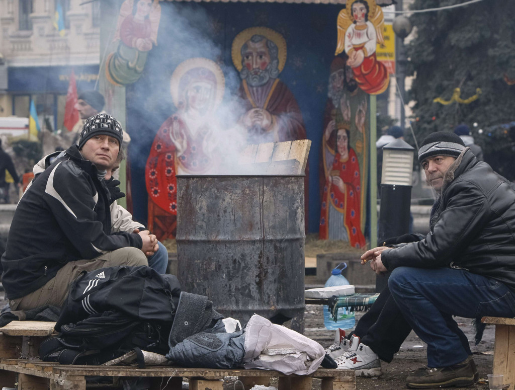 Protesters warm themselves near a fire during a rally in Independence Square in Kiev, Ukraine, Dec. 16.