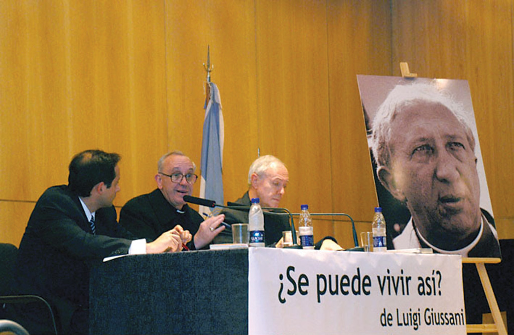 A large poster showing the face of the Italian priest and theologian, Msgr. Luigi Giussani, during a 2008 presentation of one of Giussani's books, Can We Live Like This? in Buenos Aires, Argentina. Speaking in the center is the Cardinal Archbishop of Buenos Aires, Jorge Mario Bergoglio, the future Pope Francis.