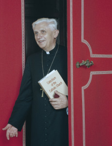 Then-Cardinal Joseph Ratzinger with a copy of the Cathechism of the Catholic Church, issued under his direction.