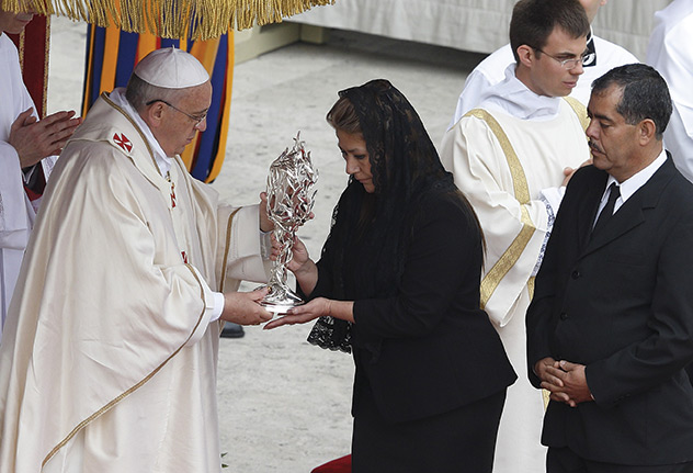 Above, Pope Francis kisses the relic of St. John XXIII presented by Father Ezio Bolis, director of the Pope John XXIII Foundation. Below, Francis gives back the relic of St. John Paul II to Floribeth Mora Diaz whose cure from an aneurysm in 2011 was the second miracle in St. John Paul's cause.