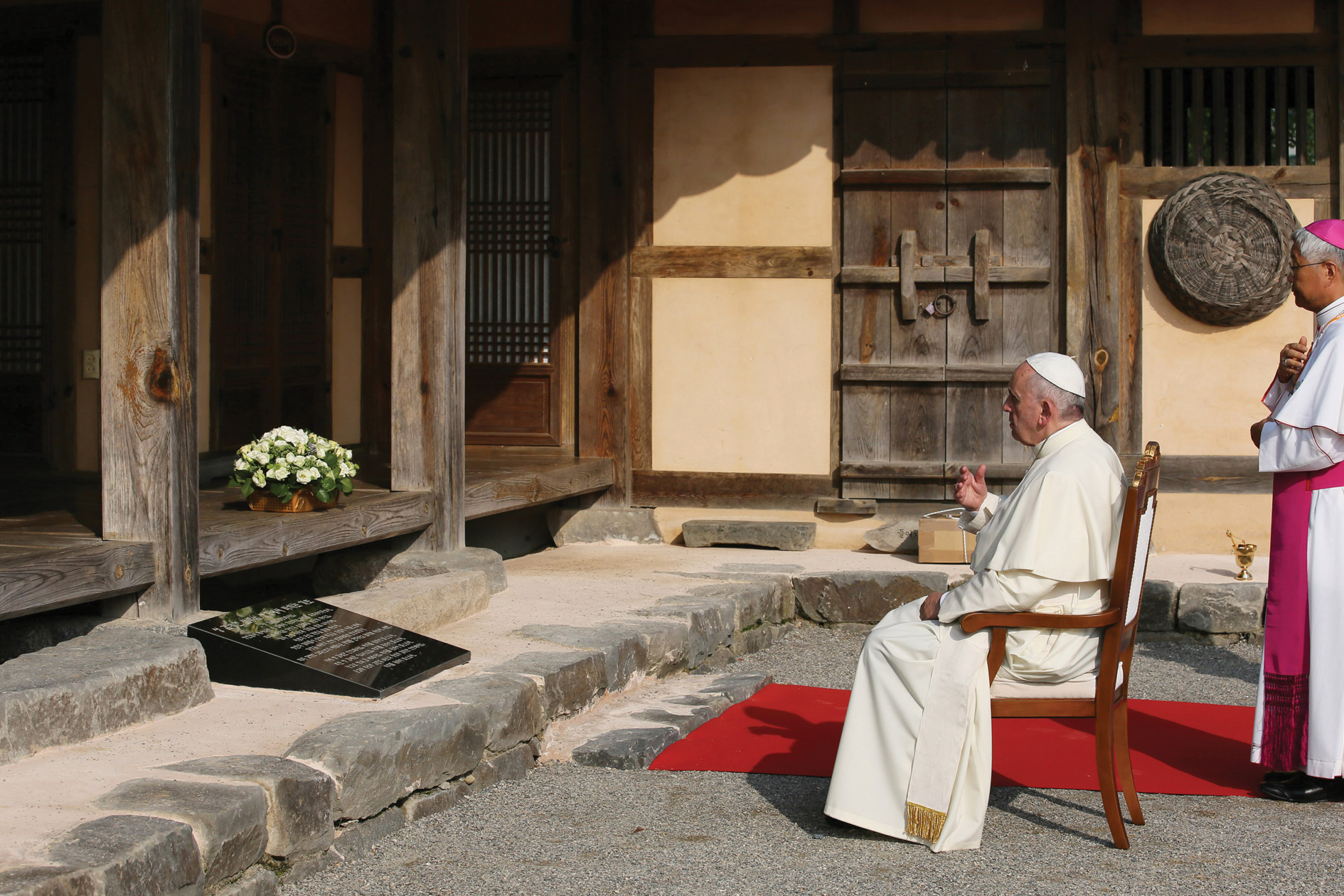 Pope Francis, after being received by the Rector of the Sanctuary, prays before the house of St. Andrew Taegon Kim, the first Korean priest.