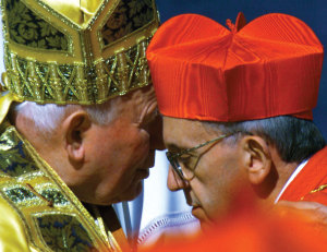Pope John Paul II embraces Argentine Cardinal Jorge Bergoglio after presenting the new cardinal with a red biretta at the Vatican in February 2001.