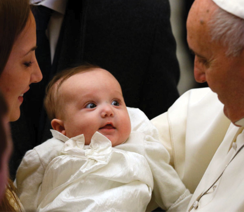 Pope Francis greets a baby while meeting newly married couples during his general audience in the Paul IV Hall at the Vatican.