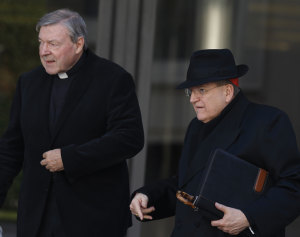 Pell and US Cardinal Raymond Burke leave a meeting in the Synod Hall at the Vatican.