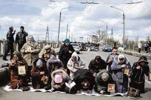 People pray for peace near a regional government building that has been seized by pro-Russian troops in Sloviansk, eastern Ukraine.