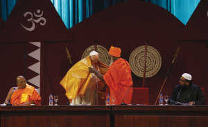 Pope Francis receives a robe from Hindu Kurukkal Siva Sri T. Mahadeva during a meeting with religious leaders.