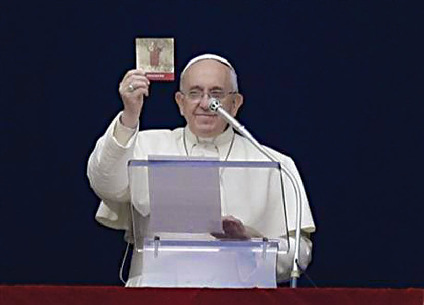 Pope Francis presents the little volume entitled 'Prayers' after his Angelus.