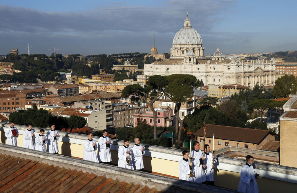 St Peter's Basilica is seen in the background as seminarians lead a procession during the dedication of a new building at the Pontifical North American College in Rome.
