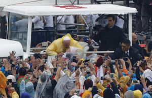 Pope Francis kisses a baby as he arrives to celebrate mass.