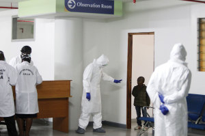 A Kenyan Port Health Services worker commands a small boy, one of nine Kenyans stranded in  Ebola-hit Liberia, to return to a observation room for Ebola screening in Jomo Kenyatta International Airport in Nairobi.