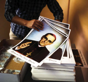 A volunteer holds posters of slain Archbishop Oscar Romero at a church in San Salvador February 3, the day Pope Francis officially recognized the prelate's martydom.