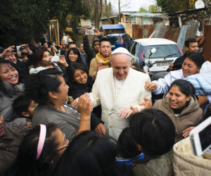 Pope Francis is greeted during a surprise visit to an immigrant settlement in Rome Feburary 8.