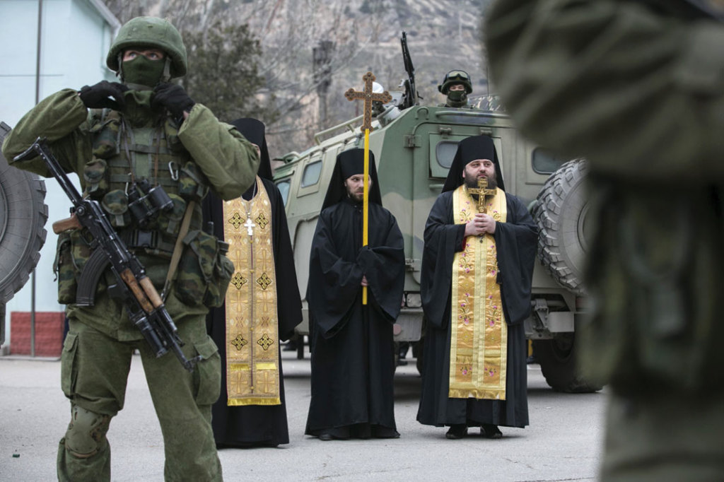 Orthodox clergymen pray near Russian army vehicles by a Ukrainian border post in Ukraine's Crimean region on March 1, 2014.