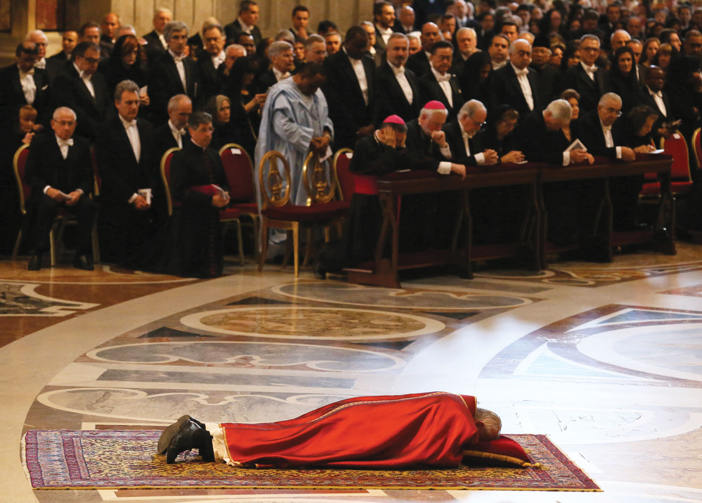 Francis lies prostrate at the start of the ceremony and, right, holds a crucifix (Galazka photos)