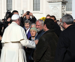 December 17, 2014, in St. Peter's Square. During the Pope's Wednesday General Audience, several homeless people greet Pope Francis on his 78th birthday, bringing sunflowers as gifts.