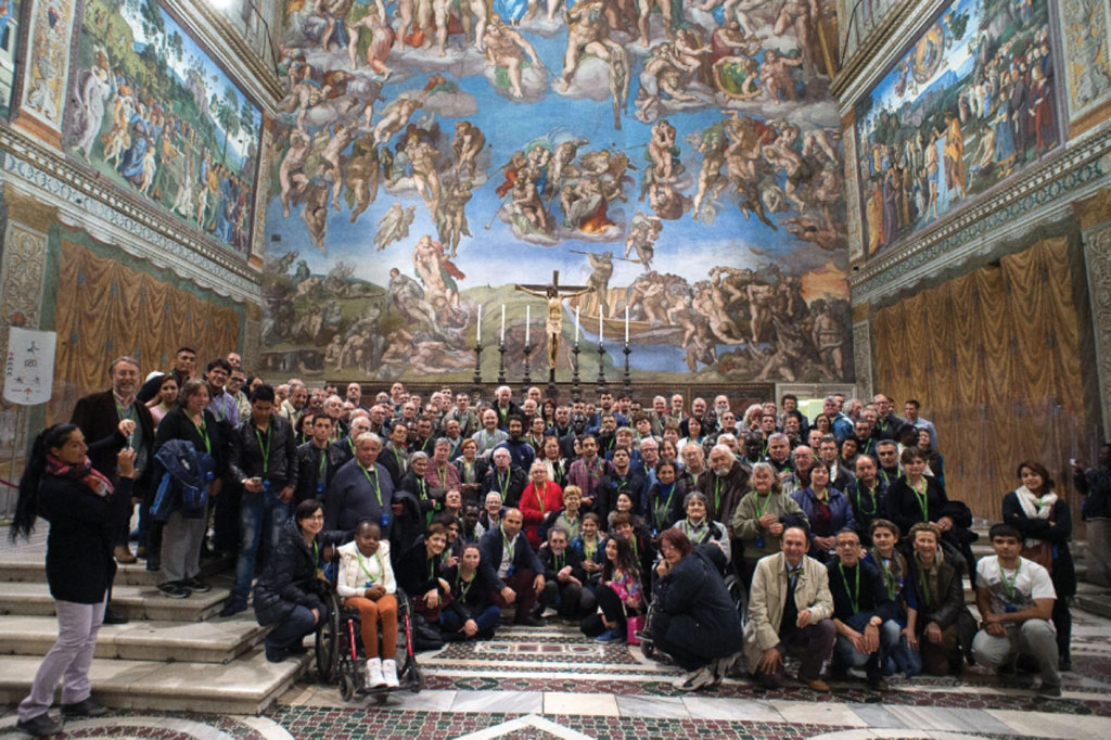 a group photo of the poor invited by the Pope into the Sistine Chapel