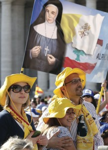 A banner showing the new Saint Marie-Alphonsine is seen as a family waits for the start of the canonization Mass for four new saints in St. Peter's Square at the Vatican May 17.