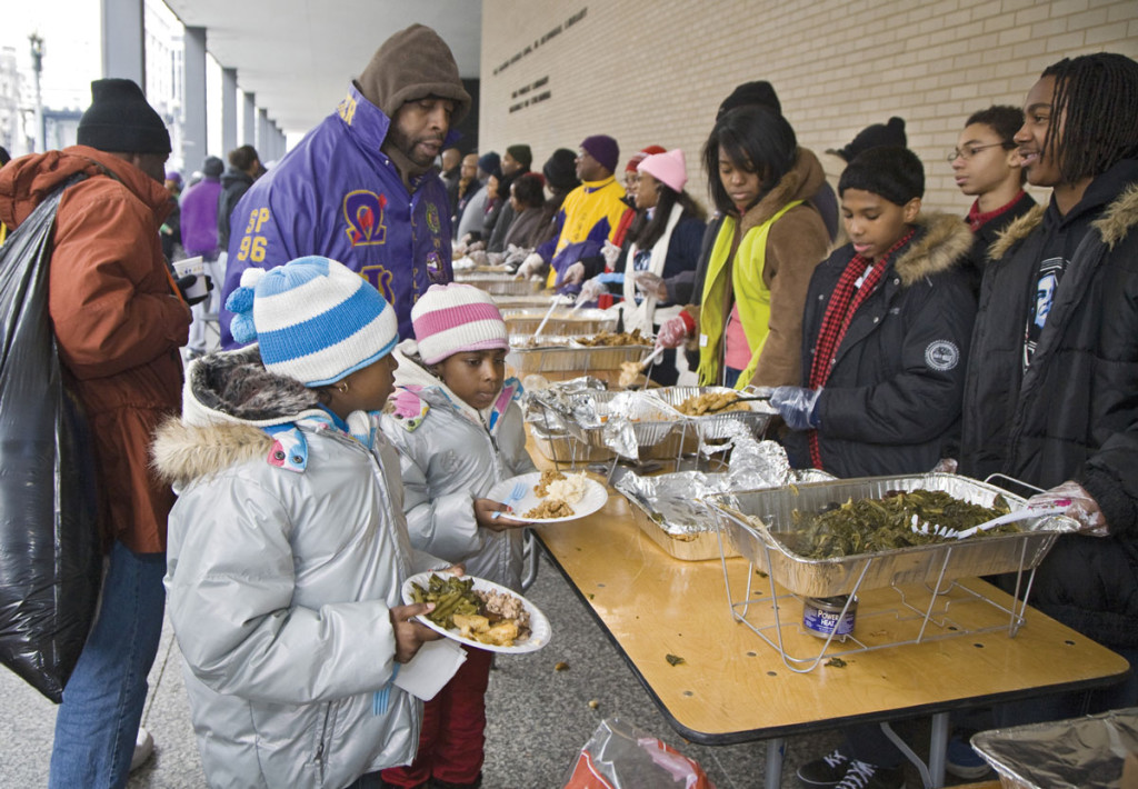 Economic adversity can destabilize family life: Two young girls receive food at an outdoor soup kitchen in Washington. During tough economic times, children bear some of the heaviest burdens because of increased family stress, according to an annual study of child well-being (CNS photo/Jim West). To the left, Aristotle and Pius XI (1922-1939)