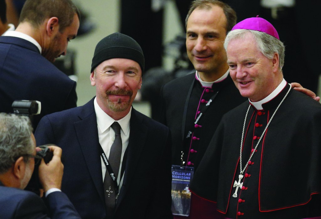 U2 guitarist David Evans, also known by his stage name The Edge, poses with Msgr. Melchor Jose Sanchez de Toca y Alameda, under secretary of the Pontifical Council for Culture, and Irish Bishop Paul Tighe, adjunct secretary of the same council, during a conference on adult stem cell research at the Vatican April 29. (CNS photo/Paul Haring) See POPE-BIDEN-CANCER April 29, 2016.