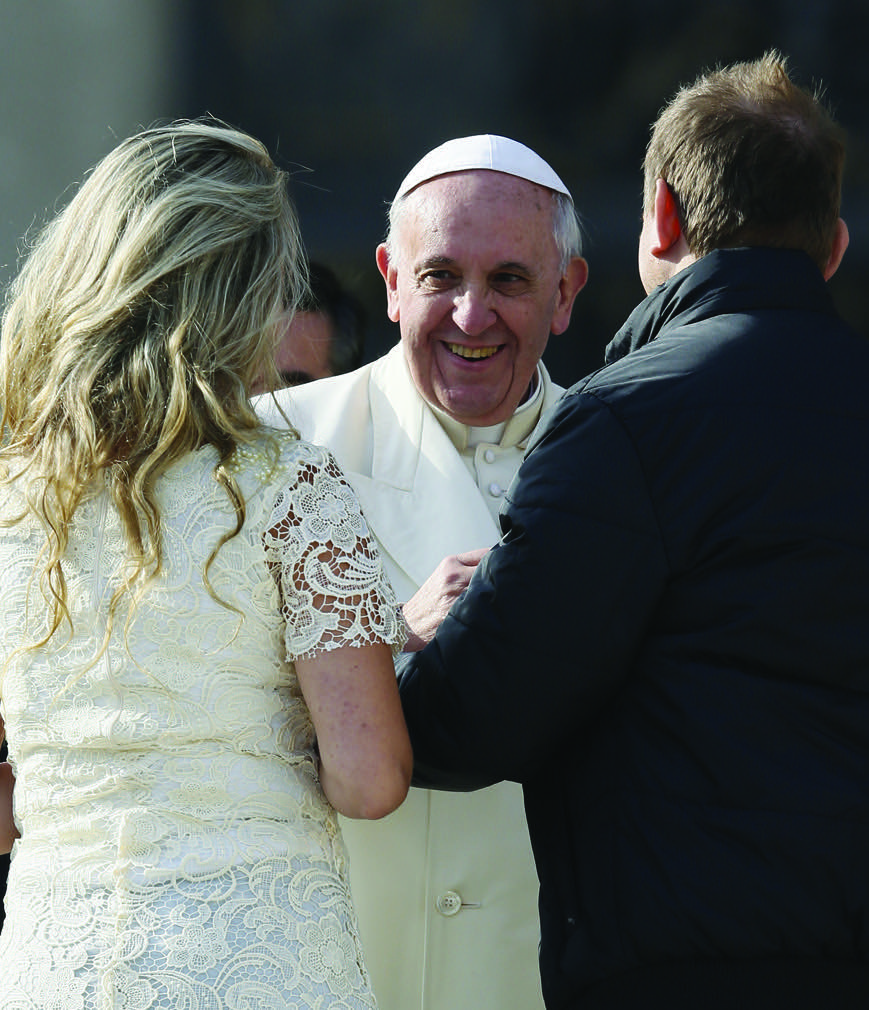 Pope Francis greets a couple at the end of his general audience in St. Peter's Square at the Vatican Jan. 8. (CNS photo/Paul Haring) (Jan. 8, 2014) See POPE-AUDIENCE Jan. 8, 2014.