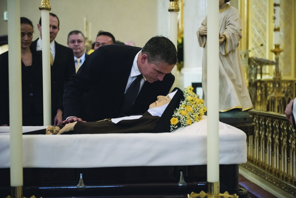 Actor Jim Caviezel pays his respects at the casket of Mother Angelica before her April 1 funeral Mass at the the Shrine of the Most Blessed Sacrament in Hanceville, Ala. Mother Angelica, who founded the Eternal Word Television Network and turned it into one of the world's largest religious media operations, died March 27 at age 92. (CNS photo/Jeffrey Bruno, EWTN) See MOTHER-ANGELICA-FUNERAL April 1, 2016.