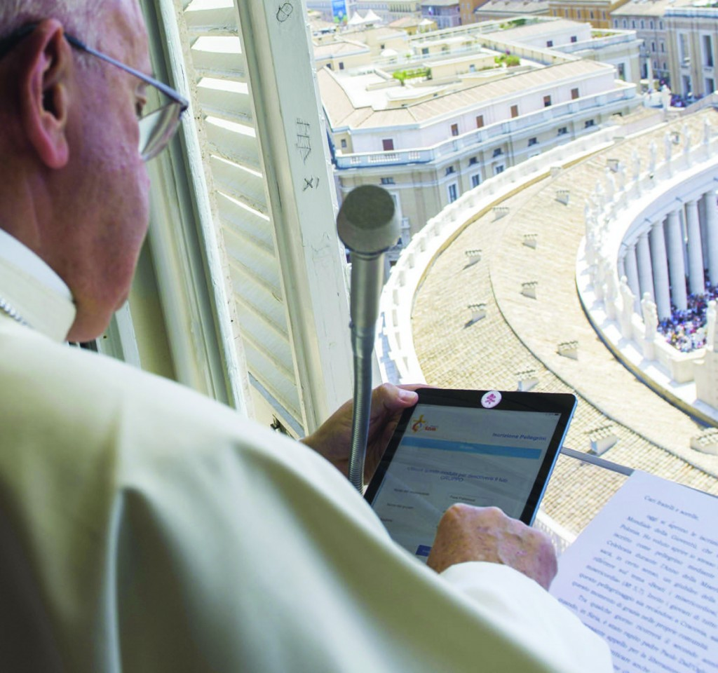 Pope Francis uses a tablet to officially open online registration for World Youth Day 2016 in Poland. He did this during the Angelus from the window of his studio overlooking St. Peter's Square at the Vatican July 26. (CNS photo/L'Osservatore Romano via EPA) See POPE-ANGELUS July 27, 2015.