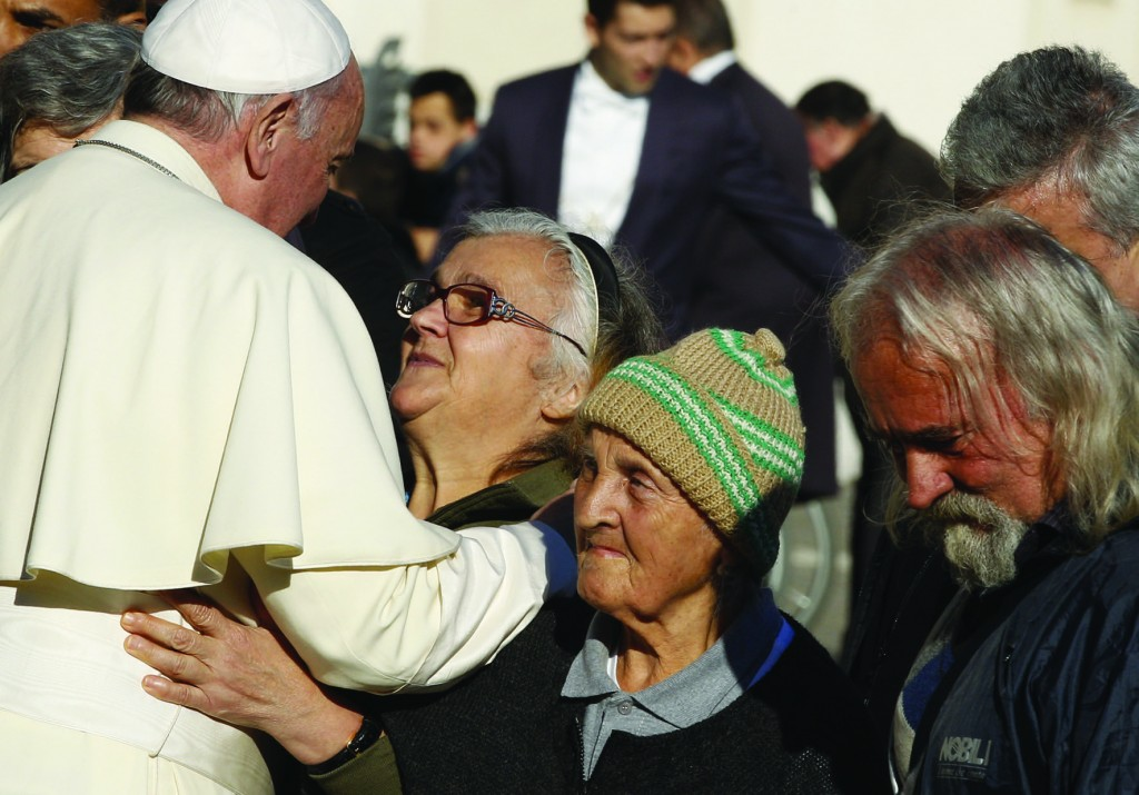 Pope Francis greets one of eight poor people at his general audience in St. Peter's Square at the Vatican Dec. 17, the pope's 78th birthday. A group of the poor were invited to the audience in celebration of the pope's birthday. (CNS photo/Paul Haring) See POPE-AUDIENCE Dec. 17, 2014.