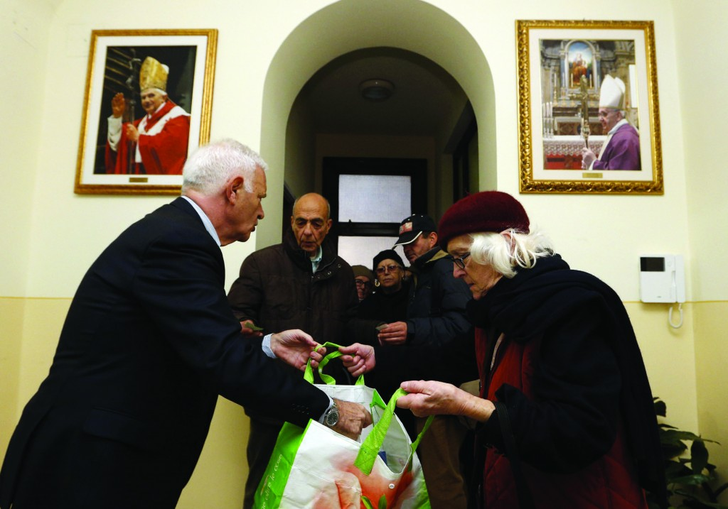 Images of Pope Benedict XVI and Pope Francis are seen as volunteers hand out gift packs to poor people after Mass at St. Anne's Parish at the Vatican Dec. 19. (CNS photo/Paul Haring)